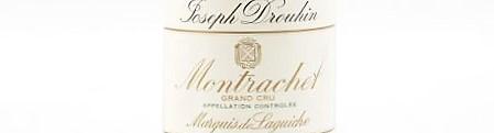 La photo montre une bouteille de vin du grand cru montrachet marquis de laguiche du Domaine joseph drouhin situé à beaune en Bourgogne