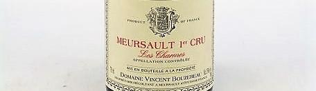 La photo montre une bouteille de vin DE MEURSAULT 1er cru les charmes du Domaine de vincent bouzereau situé dans le prieuré du chateau de meursault en Bourgogne